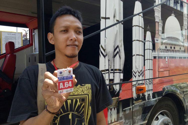 Yusuf (28) salah satu anggota komunitas Busmania wilayah Semarang, memperlihatkan kartu tiket bus tingkat wisata Semarang pada KompasTravel, Jumat (6/9/2017). Setiap perjalanannya wisatawan akan diberi kartu yang berbeda, merah untuk pagi, biru keberangkatan siang, kuning sore, dan hijau trip malam hari.