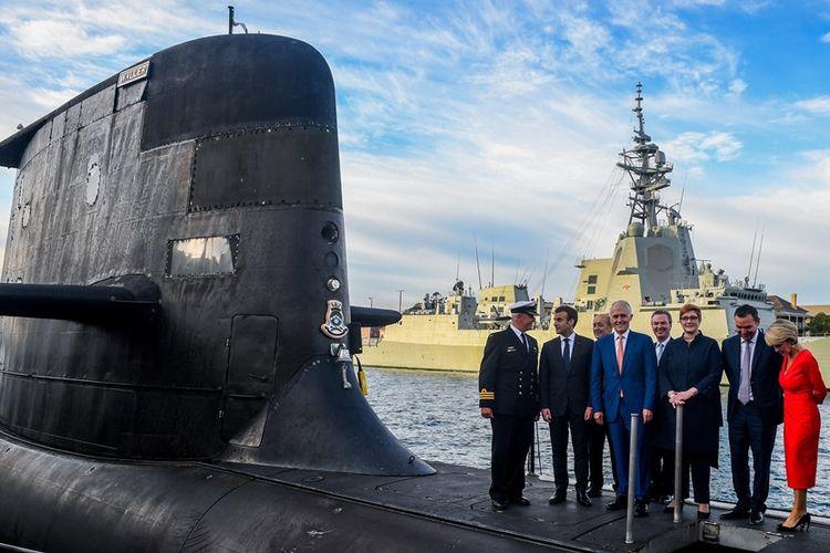 Presiden Perancis Emmanuel Macron (dua dari kiri) dan mantan Perdana Menteri Australi Malcolm Turnbull (tengah) di atas kapal selam HMAS Waller milik Angkatan Laut Australia, di Sydney, pada Mei 2018.