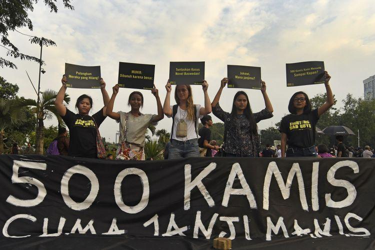 Sejumlah aktivis mengikuti aksi Kamisan ke-500 yang digelar Jaringan Solidaritas Korban untuk Keadilan di seberang Istana Merdeka, Jakarta, Kamis (27/7/2017). Dalam aksi bersama itu mereka menuntut komitmen negara hadir menerapkan nilai kemanusiaan dengan komitmennya menyelesaikan kasus-kasus pelanggaran HAM berat.