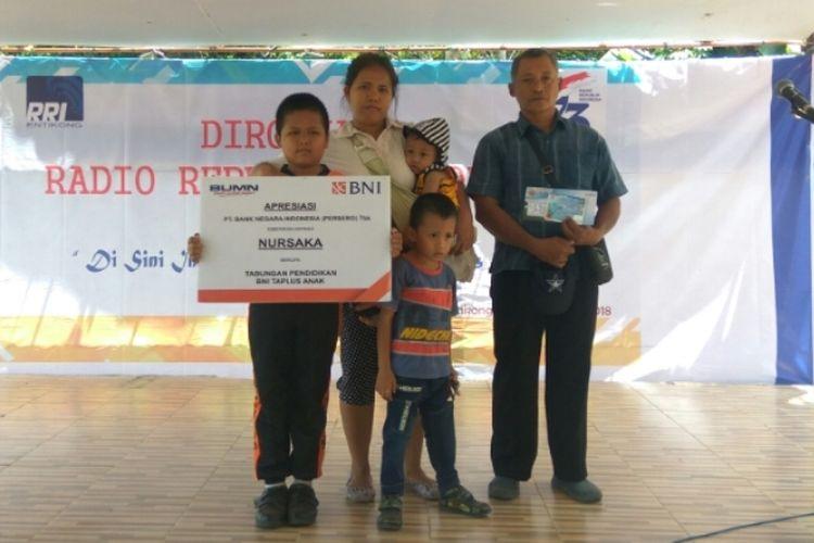 Nursaka didampingi kedua orangtuanya saat menerima beasiswa dari BNI Balai Karangan di Entikong, Kabupaten Sanggau, Kalimantan Barat, Rabu (12/9/2018).(KOMPAS.com/Yohanes Kurnia Irawan)