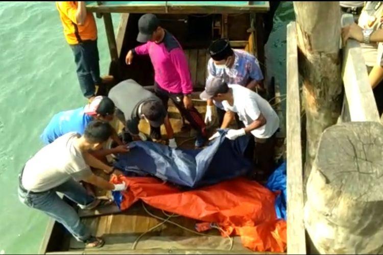Sejumlah warga bersama petugas kelurahan mengevakuasi mayat tanpa kepala yang ditemukan mengapung di perairan Desa Mapur pagi tadi.