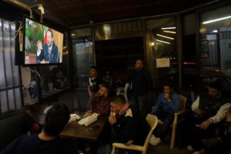Warga Lebanon menyimak pernyataan Perdana Menteri Saad Hariri melalui siaran televisi.