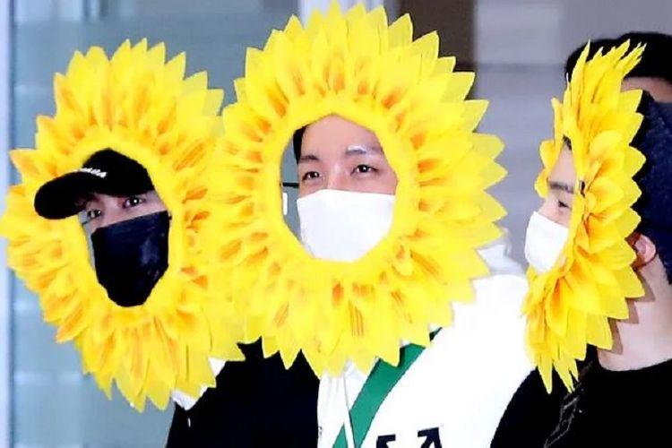 Tiga member BTS, (dari kiri) Jin, J-Hope, dan Suga, memakai hiasan kepala berbentuk kelopak bunga matahari saat tiba di bandara Icheon, Korea Selatan, Senin (10/6/2019).