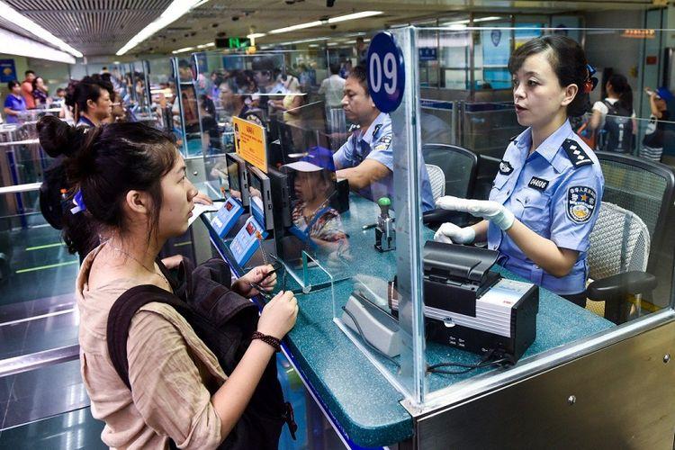 Pelancong menjalani pemeriksaan di Departemen Imigrasi di perbatasan China.