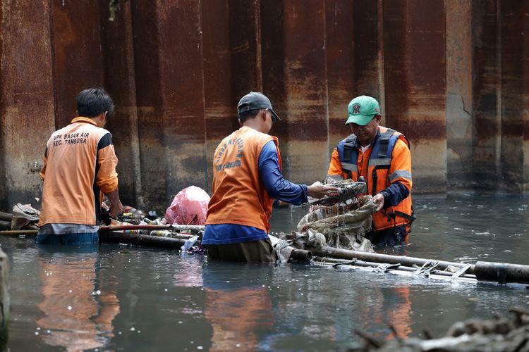 Awi Syamsudin (kanan), Pekerja Harian Lepas  UPK Badan Air Dinas Lingkungan Hidup Kecamatan Tambora membersihkan Kali Opak Perniagaan, Tambora, Jakarta Barat, Selasa (18/4/2017). KOMPAS IMAGES/KRISTIANTO PURNOMO
