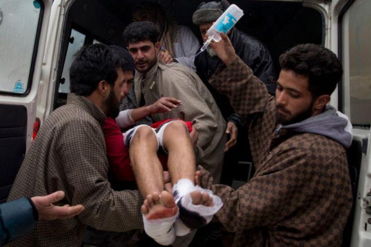 Warga membantu mengangkat tubuh siswa yang terluka akibat ledakan di dalam ruang kelas di sekolah di Kashmir, Rabu (13/2/2019).