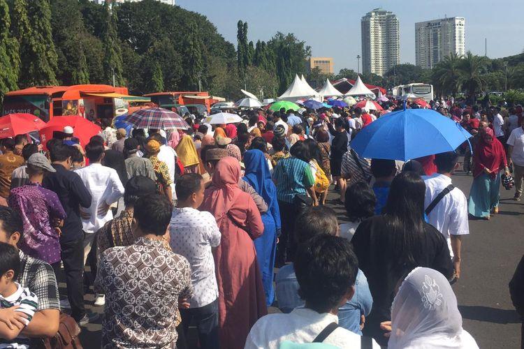 Masyarakat mengantre di pelataran Monas, Jakarta, Rabu (5/6/2019), menunggu giliran masuk ke Istana Negara guna bersilaturahmi dengan Presiden Joko Widodo pada lebaran hari pertama.