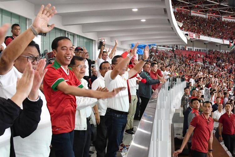 Presiden Joko Widodo mengangkat tangan menirukan gerakan suporter.