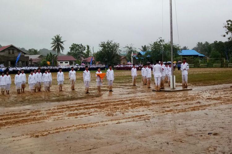 Pasukan pengibar bendera Merah Putih di Kecamatan sebulu, Kutai Kartanegara, tetap melaksanakan tugas di tengah hujan deras dan tanah yang berlumpur