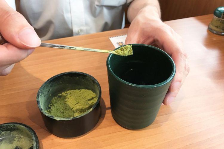 Tuang dua sendok teh hijau bubuk ke cangkir teh.