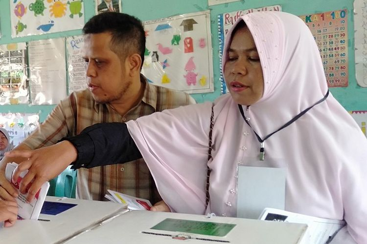 Hamdanil, seorang penyandang disabilitas memasukkan kertas suara ke kotak suara usai meyampaikan hak suaranya di TPS 5 Gampong Lamlagang Banda Aceh, Rabu (17/4/2019). Hamdanil harus dibantu pendamping karena tak tersedia template braile untuk kertas suara bagi penyandang tunanetra.