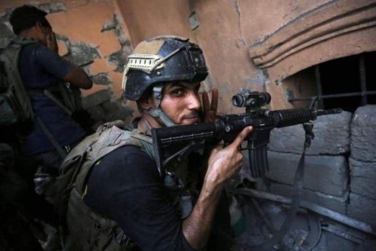 Seorang prajurit Irak mengacungkan jari membuat tanda V atau kemenangan sambil mengawasi posisi pasukan ISIS di Kota Tua Mosul.