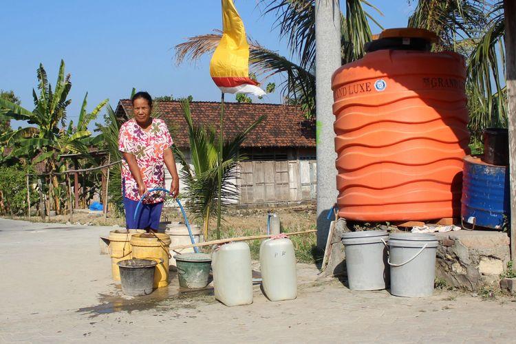 Warni (50), warga Dusun Marmoyo, Desa Marmoyo, Kecamatan Kabuh, Kabupaten Jombang, Jawa Timur, saat mengambil air di salah satu penampungan air di kampungnya, Rabu (26/6/2019).