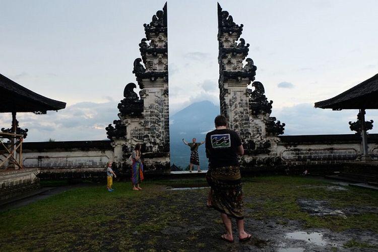 Turis berfoto dengan latar Gunung Agung dilihat dari Pura Lempuyang Luhur, Karangasem, Bali.