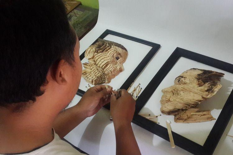 Khilmi Ardiansah saat membuat miniatur wajah Joko Widodo (kanan) dan Prabowo Subianto menggunakan batang korek api kayu, Rabu (16/1/2019)