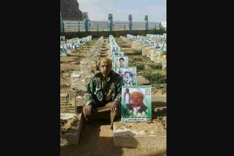 Mohammed Hussein Saleh yang membelot dari kelompok milisi Houthi berfoto di samping makamnya.