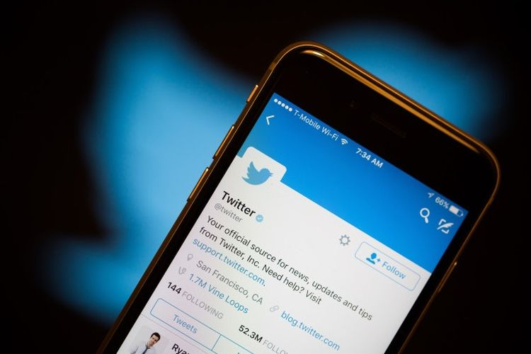 Ilustrasi Aplikasi Twitter di ponsel di depan logo Twitter