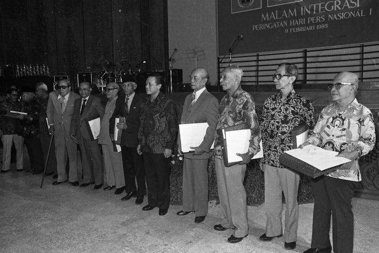 Menteri Penerangan Harmoko Sabtu malam (9/2) menyerahkan piagam dan penghargaan berupa uang masing-masing satu juta rupiah kepada 10 wartawan yang berusia lebih dari 70 tahun di Manggala Wana Bhakti. Tampak Harmoko berada di tengah ke-10 wartawan tersebut.  Judul Amplop : Integrasi Pers 1985