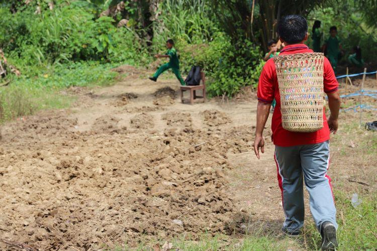 Yosep berjalan menuju ladang sambil memanggul buku dengan menggunakan ajat. Yosep merawat nasionalisme di pedalaman Kaltara dengan mendekatkan buku kepada anak.