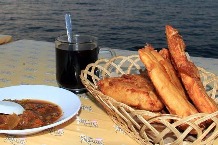 Sajian pisang goreng dan secangkir kopi sambil menikmati suasana sunset di Teluk Manado.