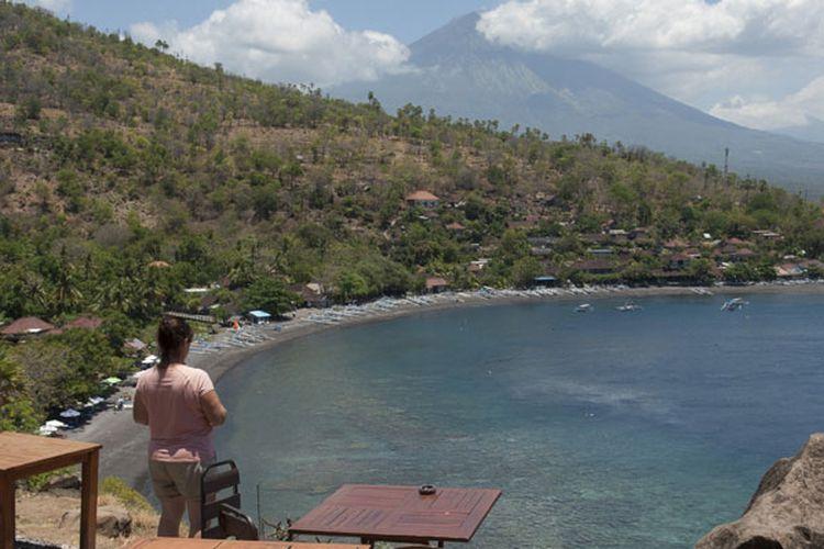 Seorang wisatawan menikmati pemandangan di Pantai Desa Amed, Karangasem, Bali, Jumat (29/9/2017). Kementerian Pariwisata menyatakan, secara umum pariwisata Bali masih normal meskipun terjadi peningkatan aktivitas Gunung Agung yang saat ini pada level awas.