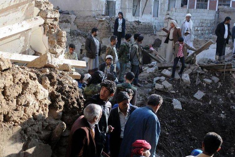 Warga sekitar memeriksa reruntuhan bangunan di kota mereka setelah serangkaian serangan udara yang dilancarkan koalisi Arab Saudi di Sanaa, Yaman.