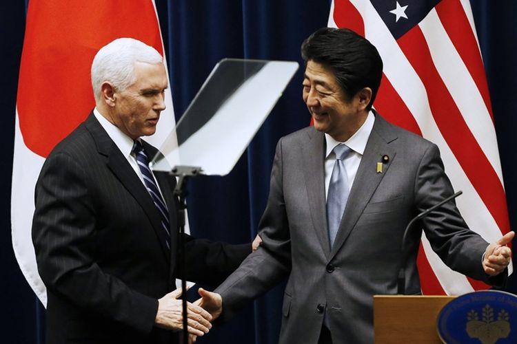 Wakil Presiden AS Mike Pence (kiri) berjabat tangan dengan Perdana Menteri Jepang Shinzo Abe usai pertemuan yang digelar di Tokyo, Rabu (7/2/2018).
