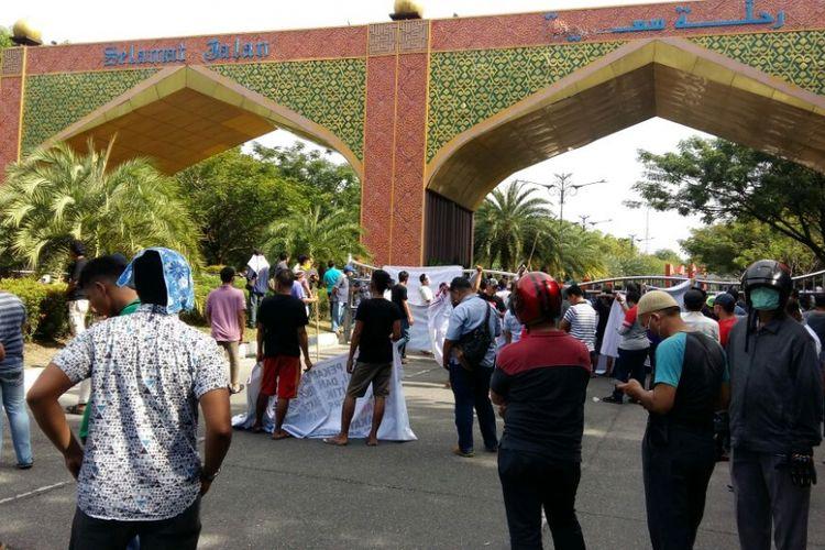 Ratusan massa memblokade gerbang Bandara SSK II Pekanbaru untuk menghadang mobil yang ditumpangi Neno Warisman, Sabtu (25/8/2018).