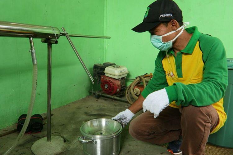 Seorang pekerja memindahkan uap hasil pembakaran batok kelapa. Usaha ini menjadi andalan bagi warga Desa Nusa Serasan, Kecamatan Sungai Lilin, Kabupaten Musi Banyuasin, Sumatera Selatan.