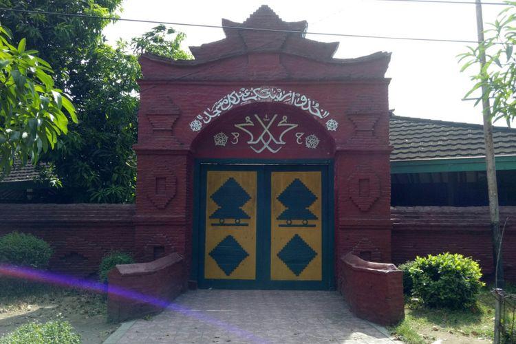 Gerbang utamanya terbuat dari susunan bata merah yang rapat dan tinggi.