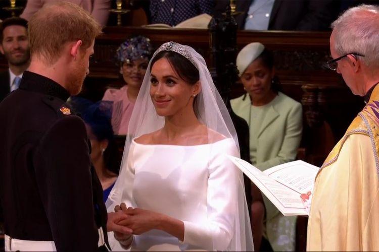 Meghan Markle menyematkan cincin pernikahan ke jari manis Pangeran Harry dalam prosesi pemberkatan nikah di Kapel St.George, Windsor, Inggris, Sabtu (19/5/2018).