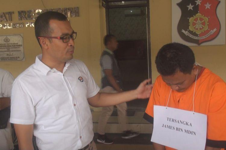 Tersangka James (baju orange) menunduk ketika ditampilkan di hadapan wartawan yang meliput di Mapolres Prabumulih