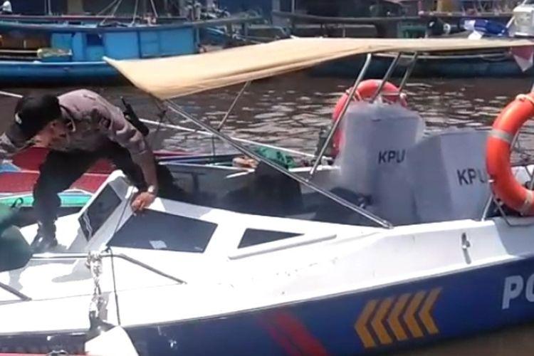 Seorang personel kepolisian memasukkan kotak suara ke speedboat untuk dikirim ke Desa Tanjung Saleh, Kakap, Kubu Raya, Kalimantan Barat, Selasa (16/4/2019).