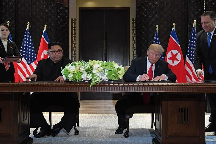 US President Donald Trump (2nd R) and North Koreas leader Kim Jong Un (2nd L) sign documents as US Secretary of State Mike Pompeo (R) and the North Korean leaders sister Kim Yo Jong (L) look on at a signing ceremony during their historic US-North Korea summit, at the Capella Hotel on Sentosa island in Singapore on June 12, 2018.  Donald Trump and Kim Jong Un became on June 12 the first sitting US and North Korean leaders to meet, shake hands and negotiate to end a decades-old nuclear stand-off. / AFP PHOTO / SAUL LOEB