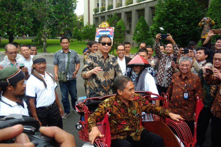 Menteri ESDM Ignatius Jonan (Kacamata Hitam) Mengendarai Becak Listrik dengan Penumpang Rektor UGM Panut Mulyono
