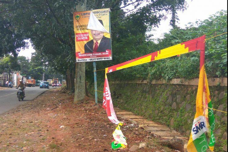 Reklame berupa tawaran cicilan rumah hingga alat peraga kampanye terlihat usang di Jalan Boulevard Grand Depok City, Kota Depok, Rabu (14/2/2018).