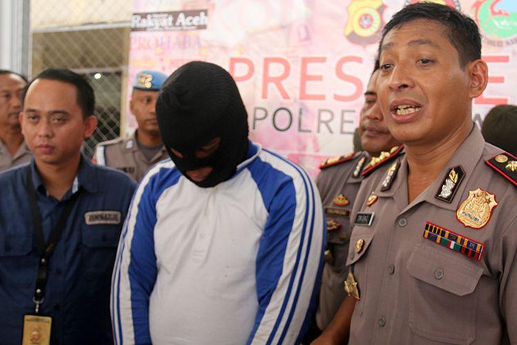 Kapolresta Banda Aceh AKBP Trisno Riyanto (kanan) bersama Kasat Reskrim AKP Taufik saat merilis kasus pemerasan dengan modus mengancam korban akan menyebarkan foto telanjang ke media sosial yang dilakukan ES (20) terhadap mantan pacarnya. Senin (16/4/2018).