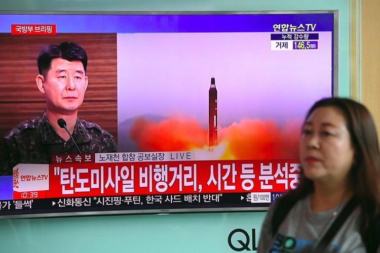 Seorang wanita berjalan melewati sebuah layar televisi yang menunjukkan cuplikan rekaman peluncuran misil balistik Korea Utara, di sebuah stasiun kereta api di Seoul, Selasa (4/7/2017). Korea Utara mengklaim uji misil balistik itu sebagai simbol kemampuan persenjataan untuk mengancam dua negara bersekutu, Korea Selatan dan Amerika Serikat.