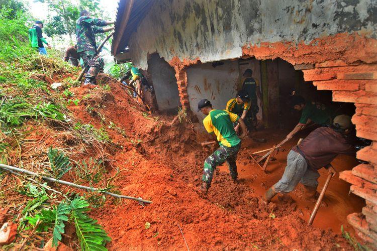 Warga bersama prajurit TNI AD dari Yonif 323/Buaya Putih Raider membersihkan lumpur atau material tanah pascalongsor yang menimpa dua rumah dan menyebabkan empat orang tewas tertimbun di Sidamulih, Kabupaten Pangandaran, Jawa Barat, Minggu (8/10). Berdasarkan data Pusdalops BPBD Pangandaran, sebanyak 17 titik terkena bencana banjir dan tanah longsor. Warga yang terkena dampak mengungsi di rumah saudara, tempat ibadah, Puskesmas dan balai desa setempat.
