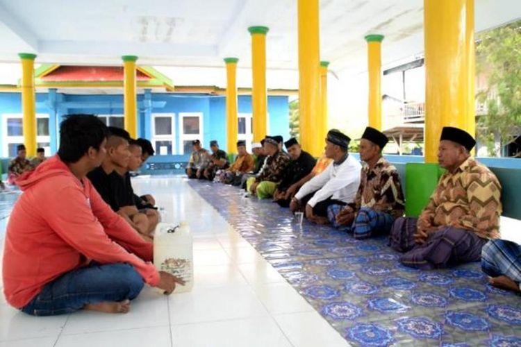 Para tokoh adat Desa Dongkala dan Desa Kondowa (menggunakan kopiah) memberikan sanksi adat kepada para pemuda yang kedapatan menjual dan konsumsi minuman keras.