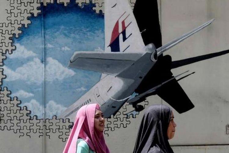 Dua warga melintas di depan mural hilangnya pesawat Malaysia Airlines MH370 di sebuah gang di Shah Alam, Malaysia, 8 Maret 2016.