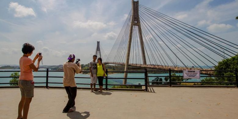 Warga berfoto dengan latar belakang pemandangan Jembatan Barelang di Batam, Kepulauan Riau, Minggu (8/2/2015). Jembatan ini merupakan satu dari enam jembatan yang dibangun untuk menghubungkan enam pulau di Batam, yaitu Pulau Batam, Pulau Tonton, Pulau Nipah, Pulau Rempang, Pulau Galang dan Pulau Galang Baru.