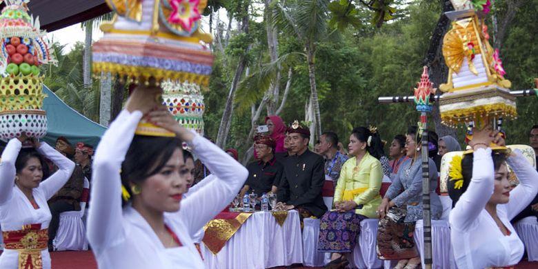 Presiden Joko Widodo (ketiga kanan), Ibu Negara Iriana Joko Widodo (kanan) dan Gubernur Bali I Wayan Koster (kiri) menyaksikan ritual Banten Gebogan saat Karnaval Budaya Bali di kawasan Nusa Dua, Bali, Jumat (12/10/2018). Karnaval tersebut merupakan rangkaian acara dari Pertemuan Tahunan IMF - World Bank Group 2018 di Bali.