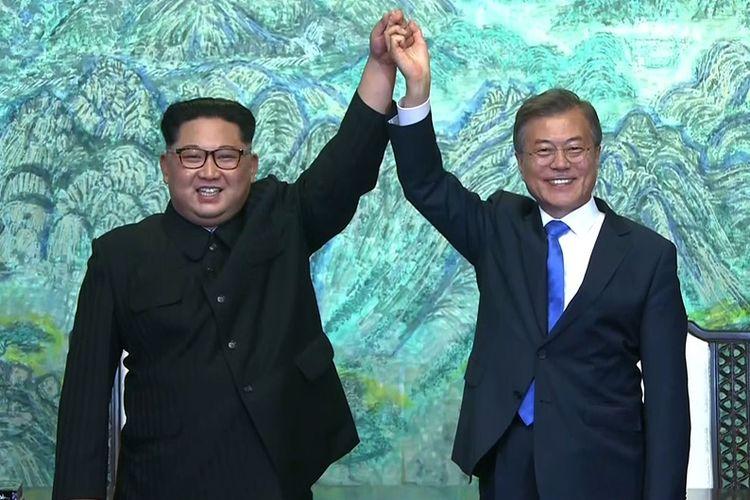 Pemimpin Korea Utara Kim Jong Un (kiri), dan Presiden Korea Selatan Moon Jae In berpegangan tangan dalam Konferensi Tingkat Tinggi (KTT) Antar-Korea di Panmunjom, Jumat (27/4/2018).