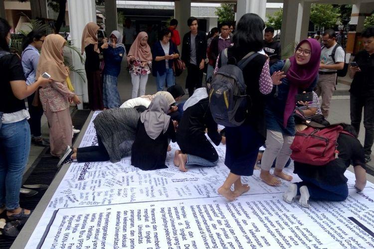Para mahasiswa saat membubuhkan tanda tangan di sebuah Baliho dalam aksi di Taman San Siro Fisipol UGM.