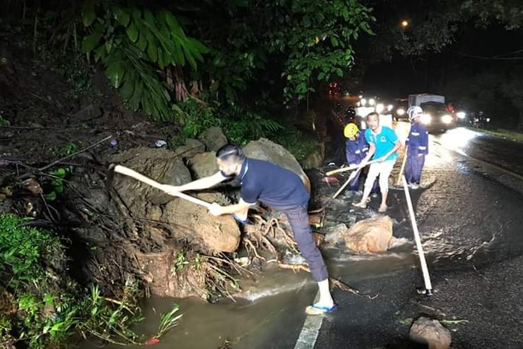 Petugas membersihkan material longsor di jalan nasional Padang-Padang Panjang, Jumat (14/6/2019) malam.