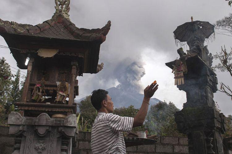 Warga berdoa di rumahnya di Desa Besakih, Karangasem, Bali, Selasa (28/11/2017). Pusat Vulkanologi dan Mitigasi Bencana Geologi memantau kolom abu gunung bertambah tinggi hingga 4.000 meter dalam enam jam terakhir sejak pukul 06.00 Wita pada Selasa (28/11/2017).
