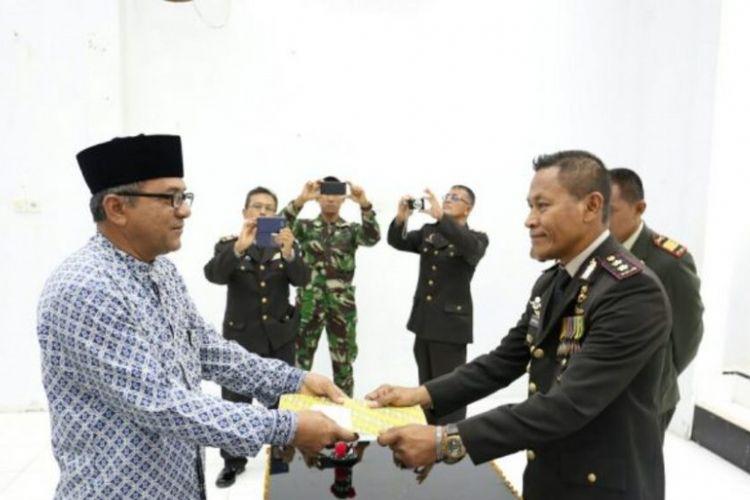Kapolres Aceh Utara AKBP Untung Sangaji menyerahkan surat tanah untuk Teuku Ramli, cucu dari pahlawan nasional Cut Meutia, di Mapolres Aceh Utara, 10 November 2017.