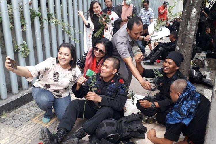 Warga memberikan bunga mawar kepada personil Brimob yang bertugas di Kantor Bawaslu RI, Jakarta Pusat, Kamis (23/5/2019).