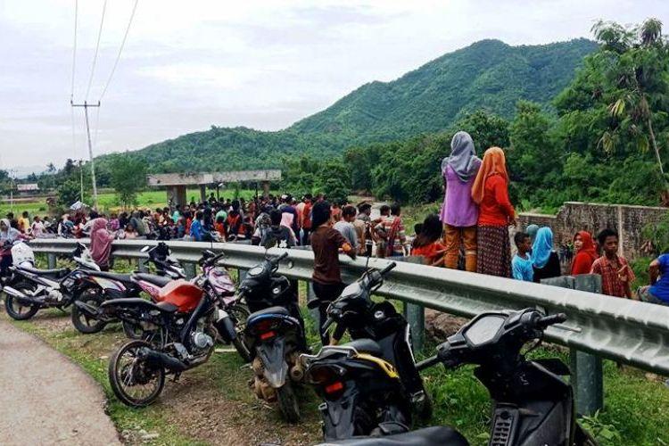 Warga memadati jembatan di bendungan Desa Soki, Kecamatan Belo, Kabupaten Bima, saat tim gabungan melakukan pencarian korban hilang terseret banjir, Minggu (14/01/2018)